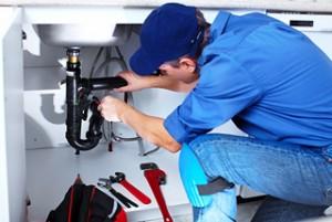 plumber making repairs under sink
